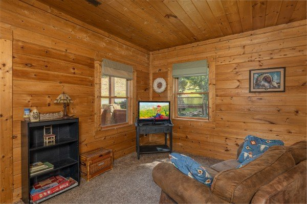 TV, bookshelf with games, and loveseat at A Beary Nice Cabin, a 2 bedroom cabin rental located in Pigeon Forge