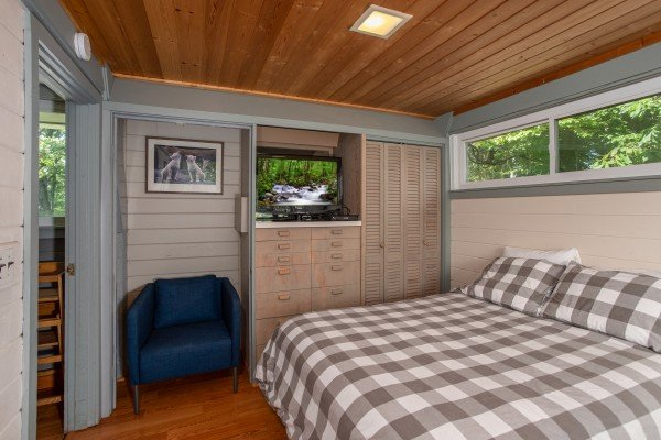 Lower queen bedroom with built ins and TV at Terrace Garden Manor, a 13 bedroom cabin rental located in Gatlinburg
