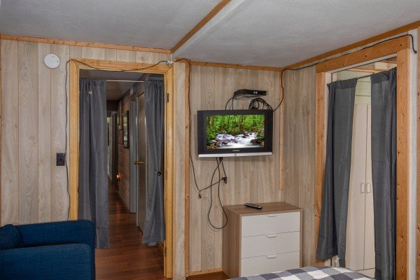 TV and small dresser in the lower floor bedroom at Terrace Garden Manor, a 13 bedroom cabin rental located in Gatlinburg