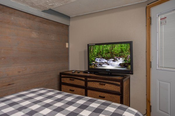 Bedroom with a bed, dresser, TV, and patio access at Terrace Garden Manor, a 13 bedroom cabin rental located in Gatlinburg