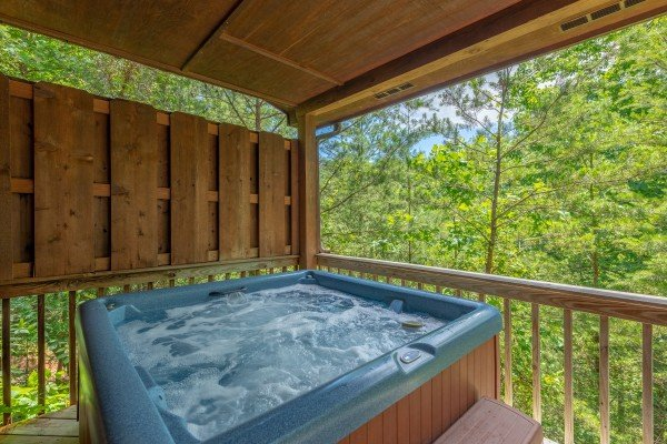 Hot tub on a covered deck at Hello Dolly, a 1 bedroom cabin rental located in Pigeon Forge