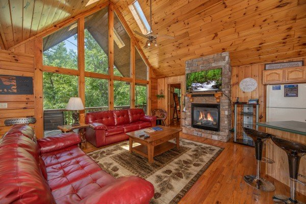 Main room with sofas, fireplace, TV, and kitchen at Hello Dolly, a 1 bedroom cabin rental located in Pigeon Forge