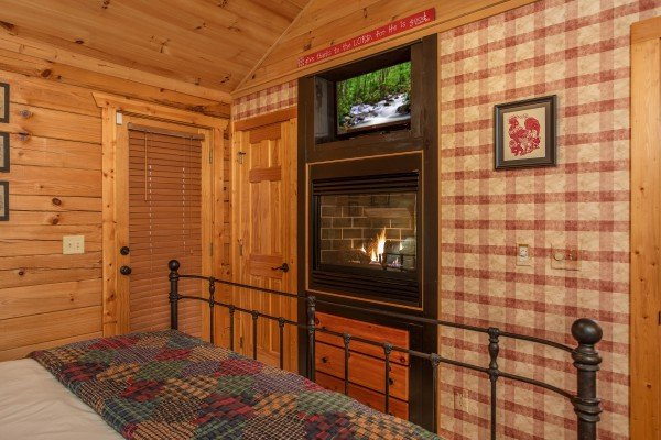 Fireplace and TV in the bedroom at Fowl Play, a 1 bedroom cabin rental located in Pigeon Forge