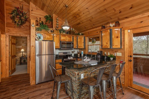 Dining at the breakfast bar in the kitchen at Fowl Play, a 1 bedroom cabin rental located in Pigeon Forge