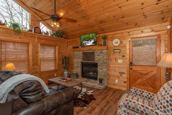 Living room with fireplace and TV at Fowl Play, a 1 bedroom cabin rental located in Pigeon Forge