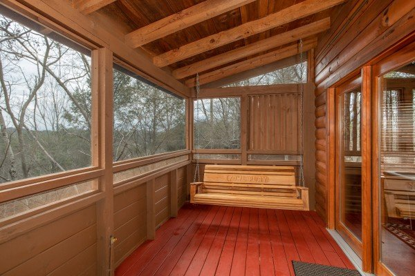 Porch swing on the screened deck at Fowl Play, a 1 bedroom cabin rental located in Pigeon Forge