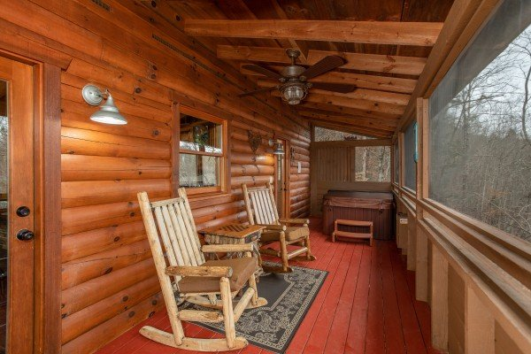 Screened porch with rocking chairs and a hot tub at Fowl Play, a 1 bedroom cabin rental located in Pigeon Forge