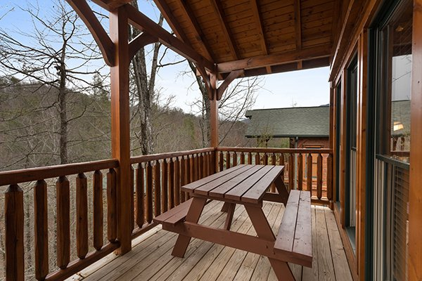 Picnic table on the covered deck at Heaven's Dew, a 1-bedroom cabin rental located in Gatlinburg
