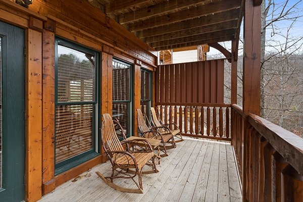 Three rocking chairs on a covered deck next to a privacy fence at Heaven's Dew, a 1-bedroom cabin rental located in Gatlinburg