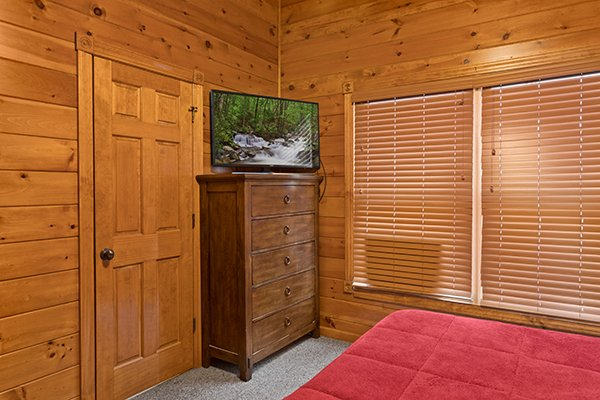 Bedroom with a chest of drawers and a TV at Heaven's Dew, a 1-bedroom cabin rental located in Gatlinburg