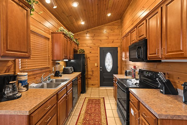 Galley kitchen with black appliances at Heaven's Dew, a 1-bedroom cabin rental located in Gatlinburg