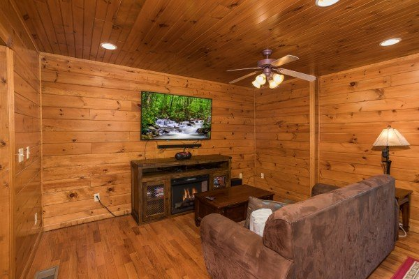 Large TV near the sleeper sofa in the game room at Heaven's Dew, a 1-bedroom cabin rental located in Gatlinburg
