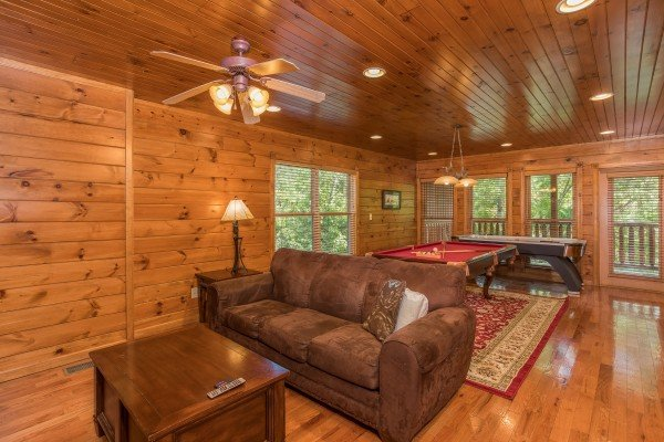 Sleeper sofa in the game room at Heaven's Dew, a 1-bedroom cabin rental located in Gatlinburg