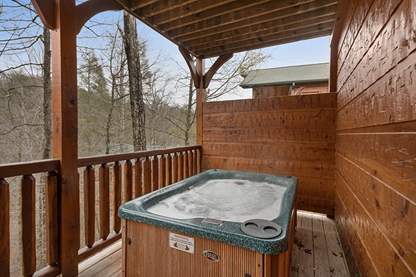 Hot tub on a covered deck with a privacy fence at Heaven's Dew, a 1-bedroom cabin rental located in Gatlinburg