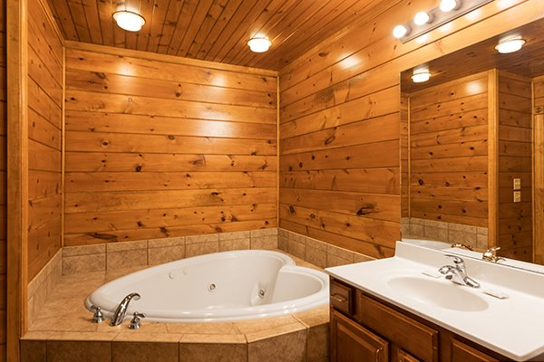 Heart-shaped jacuzzi in a bathroom at Heaven's Dew, a 1-bedroom cabin rental located in Gatlinburg