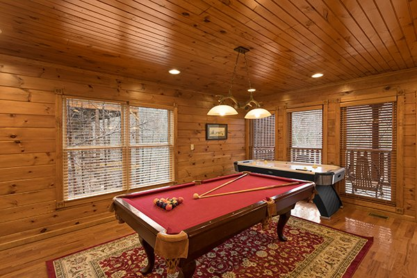 Pool table and air hockey table in the game room at Heaven's Dew, a 1-bedroom cabin rental located in Gatlinburg