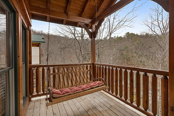Porch swing on a covered deck with wooded views at Heaven's Dew, a 1-bedroom cabin rental located in Gatlinburg