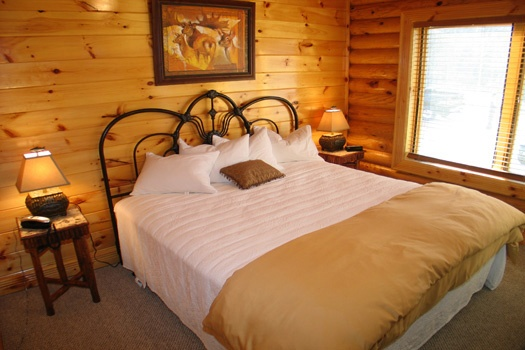 king sized bed in bedroom at gone fishin' a 2 bedroom cabin rental located in pigeon forge