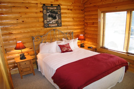 Queen sized bed in bedroom at Gone Fishin', a 2-bedroom cabin rental located in Pigeon Forge