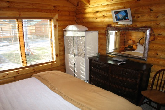 TV mounted above drawers in bedroom at Gone Fishin', a 2-bedroom cabin rental located in Pigeon Forge