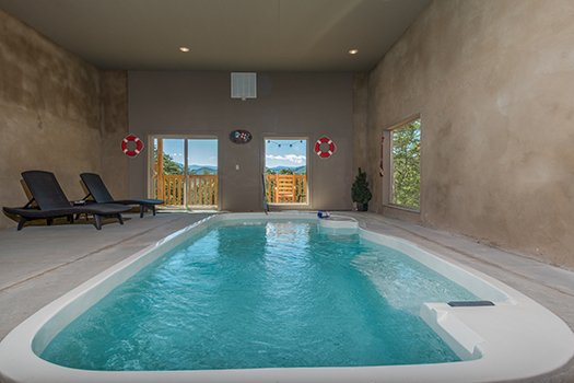 Indoor pool with two chaise lounge chairs at Canyon Camp Falls, a 2-bedroom cabin rental located in Pigeon Forge