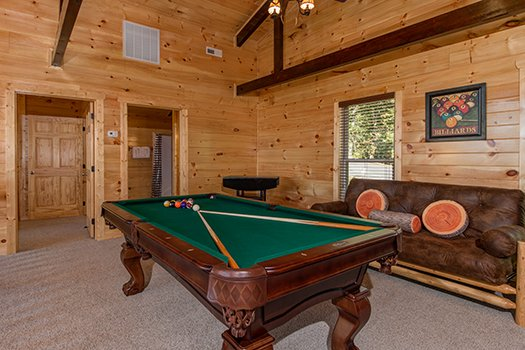 Green felted pool table and a futon in the game room at Canyon Camp Falls, a 2-bedroom cabin rental in Pigeon Forge