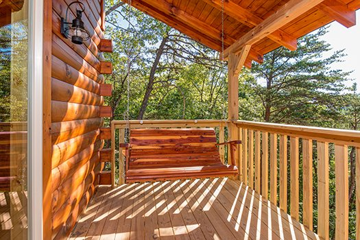 Swing on a covered deck at Canyon Camp Falls, a 2-bedroom cabin rental in Pigeon Forge