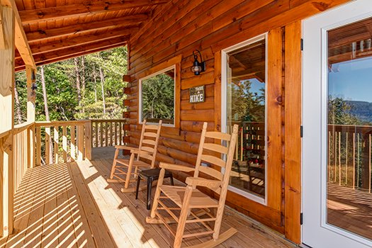 Two rocking chairs on a covered deck at Canyon Camp Falls, a 2-bedroom cabin rental in Pigeon Forge