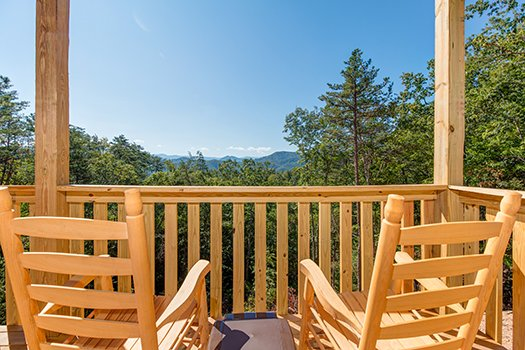 Rocking chairs on a deck overlooking the mountains at Canyon Camp Falls, a 2-bedroom cabin rental in Pigeon Forge