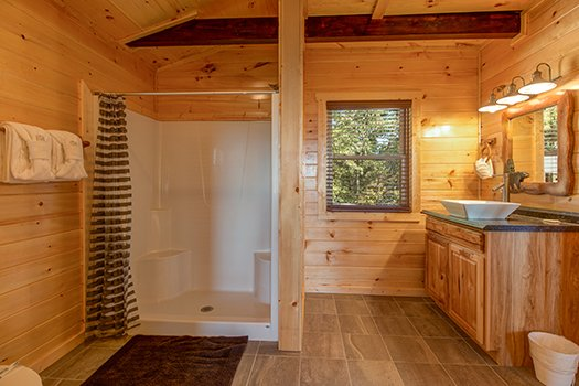 Bathroom with a large shower with built in seating at Canyon Camp Falls, a 2-bedroom cabin rental in Pigeon Forge