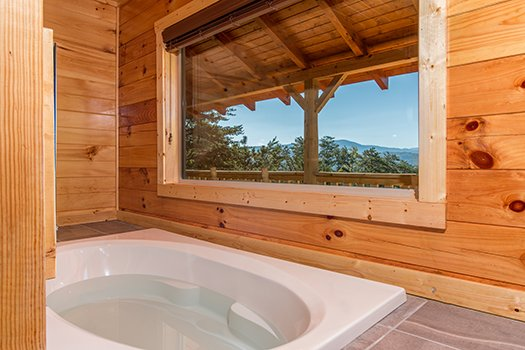 Jacuzzi with mountain views on one side and a fireplace on the other at Canyon Camp Falls, a 2-bedroom cabin rental located in Pigeon Forge