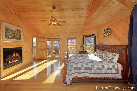 King size bed and fireplace in bedroom at About Time, a 2 bedroom cabin rental located in Pigeon Forge