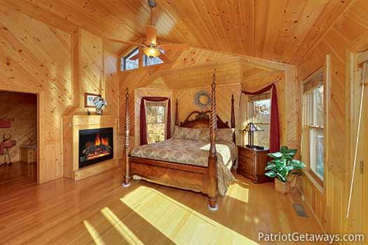 Bedroom with king sized bed and 2 way fireplace at About Time, a 2 bedroom cabin rental located in Pigeon Forge