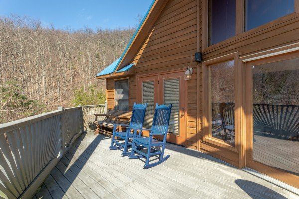 Blue rocking chairs on a deck at About Time, a 2 bedroom cabin rental located in Pigeon Forge