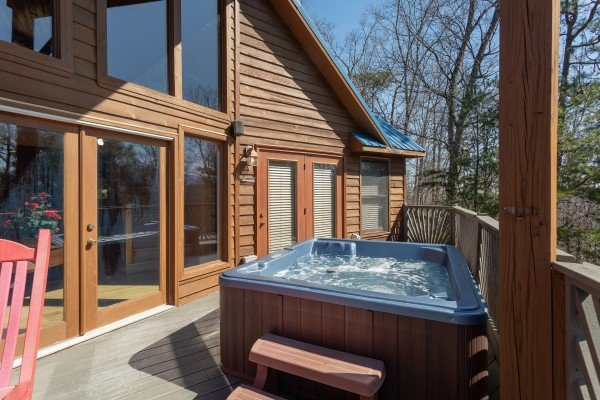 Hot tub on a covered deck at About Time, a 2 bedroom cabin rental located in Pigeon Forge