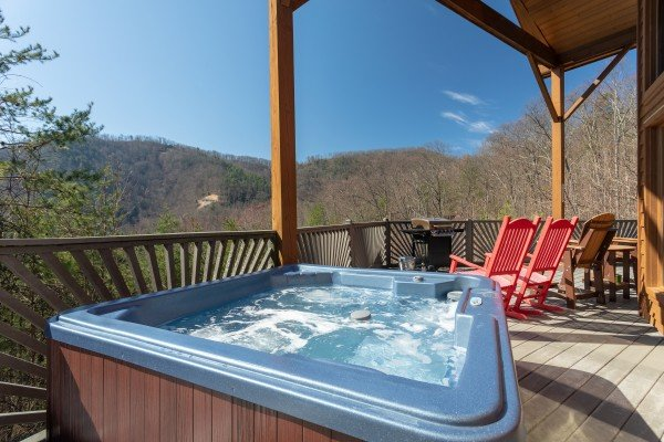 Hot tub, rocking chairs, and mountain views from the deck at About Time, a 2 bedroom cabin rental located in Pigeon Forge