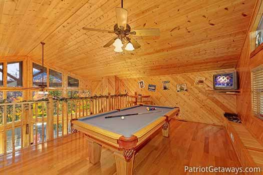 Lofted game room with pool table and tv at About Time, a 2 bedroom cabin rental located in Pigeon Forge