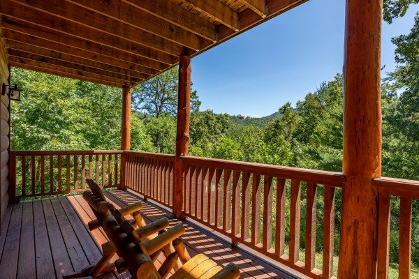 Chairs on a covered deck at The Great Outdoors, a 3 bedroom cabin rental located in Pigeon Forge