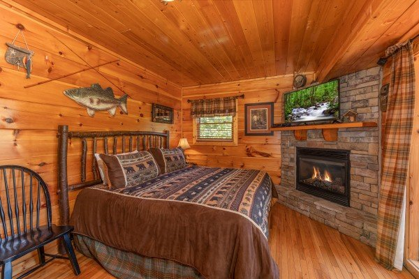 Fireplace & TV in the bedroom at The Great Outdoors, a 3 bedroom cabin rental located in Pigeon Forge