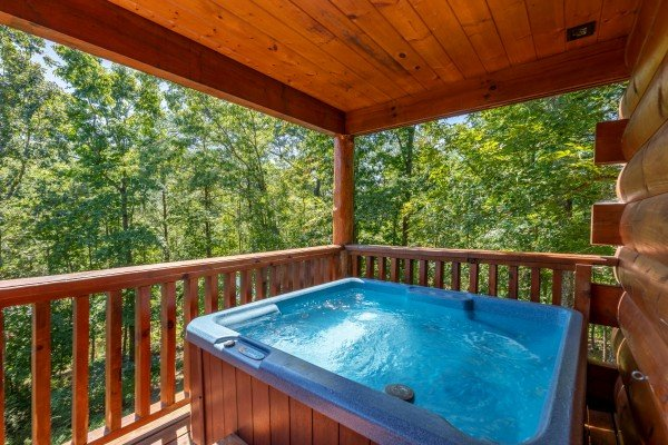 Hot tub on a covered porch at The Great Outdoors, a 3 bedroom cabin rental located in Pigeon Forge