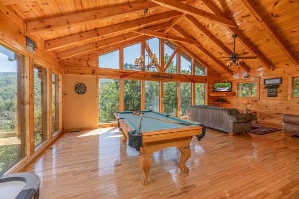Pool table and living room on the third floor at The Great Outdoors, a 3 bedroom cabin rental located in Pigeon Forge