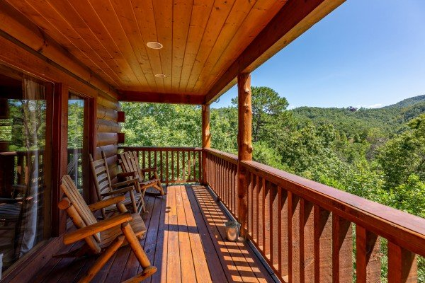 Covered deck with rocking chairs at The Great Outdoors, a 3 bedroom cabin rental located in Pigeon Forge