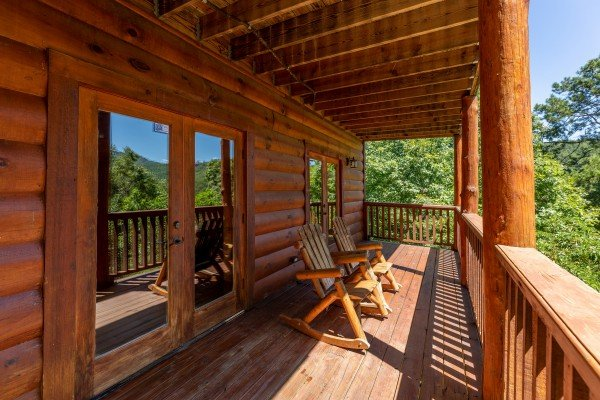 Rocking chairs on a covered deck at The Great Outdoors, a 3 bedroom cabin rental located in Pigeon Forge