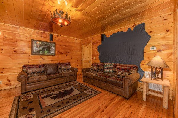 Two sofas in the theater room at The Great Outdoors, a 3 bedroom cabin rental located in Pigeon Forge