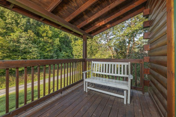 White bench on a covered deck at Family Getaway, a 4 bedroom cabin rental located in Pigeon Forge