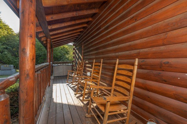 Rocking chairs on a covered deck at Family Getaway, a 4 bedroom cabin rental located in Pigeon Forge