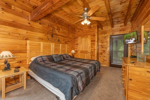 Bedroom with two night stands, lamps, dresser, TV, and deck access at Family Getaway, a 4 bedroom cabin rental located in Pigeon Forge