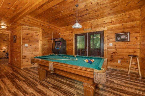 Pool table and arcade game at Family Getaway, a 4 bedroom cabin rental located in Pigeon Forge