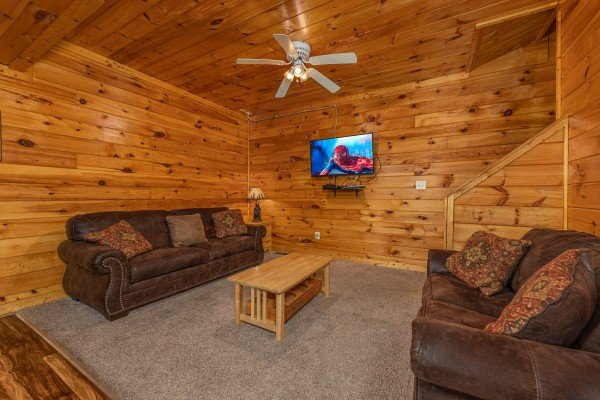 Two sofas and a TV in the game room at Family Getaway, a 4 bedroom cabin rental located in Pigeon Forge