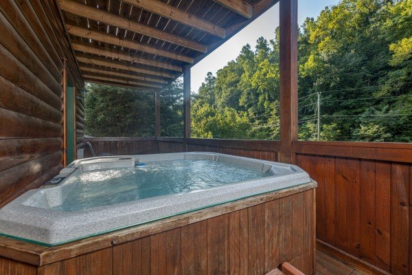 Hot tub with privacy fence on a covered deck at Family Getaway, a 4 bedroom cabin rental located in Pigeon Forge